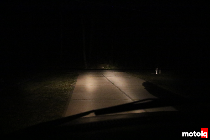 looking out front windshield seeing dim beam pattern of headlights on driveway