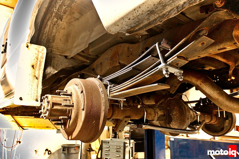 fully installed helper spring stack on top of existing leaf springs with axle, differential, and new swaybar in background