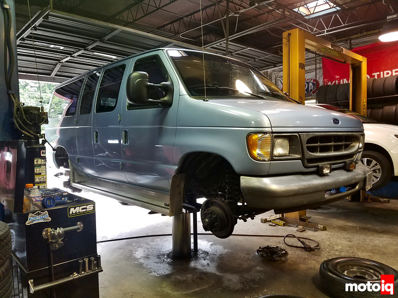 baby blue E350 van on hydraulic center post lift without wheels