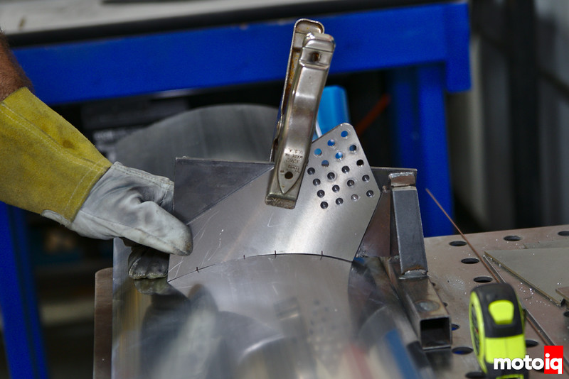 jig and welding-gloved hand holding mounting plate against wing body