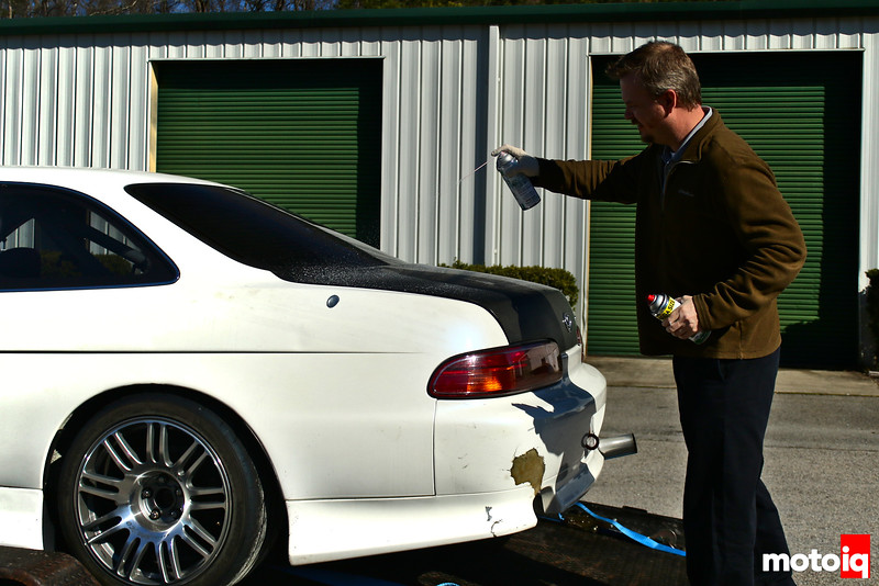 man holding spray can in one hand and spraying with another spray can with the other hand onto the car trunk