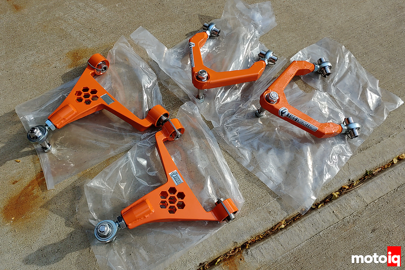four bright orange upper control arms with shiny rod ends