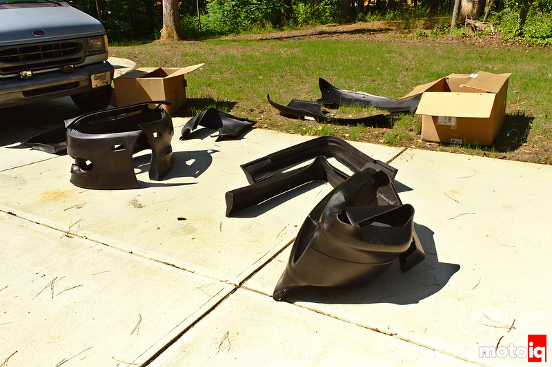 Body kit parts folded up and cardboard boxes all strewn about sunny driveway