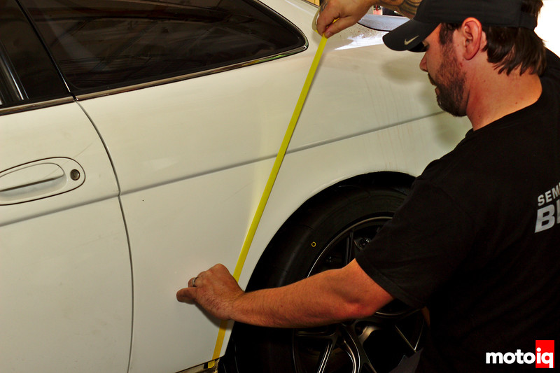 guy applying thin tape in a round arc to the rear quarter panel