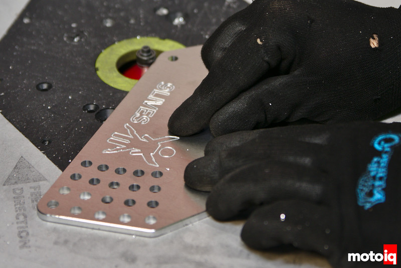 small aluminum plate being run on routing table, 9 lives racing logo visible and lots of mounting holes