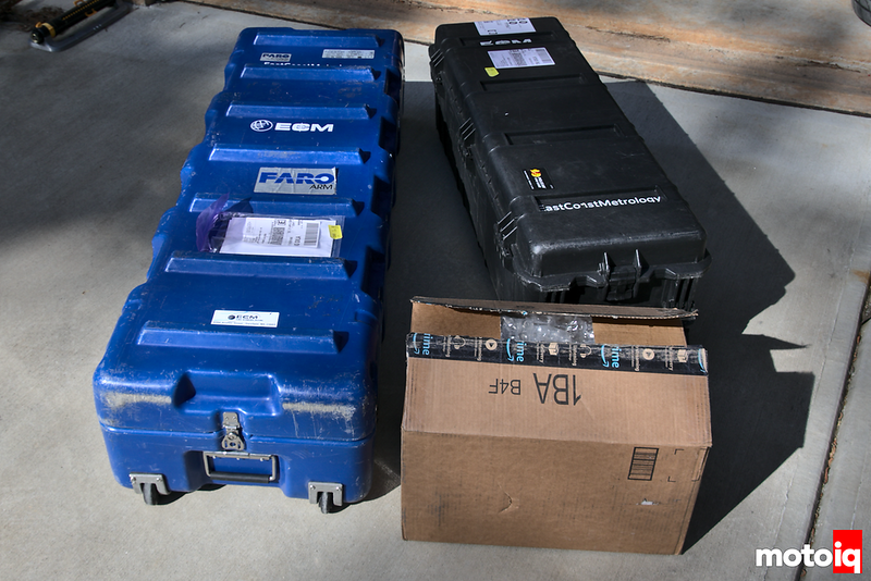 large blue and large black hard wheeled cases and a cardboard box on the pavement