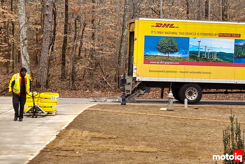 DHL truck in background with guy pulling pallet up the driveway