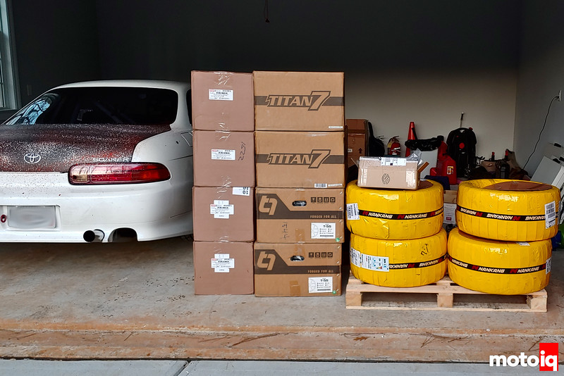 StopTech Brakes boxes, Titan7 Wheels boxes, Figs Engineering boxes, and yellow tape-wrapped Nankang tires on a pallet