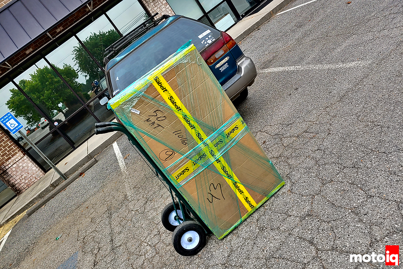 really large cardboard box with yellow Sabelt logo tape and some shrink wrap on a hand truck sitting in a parking lot
