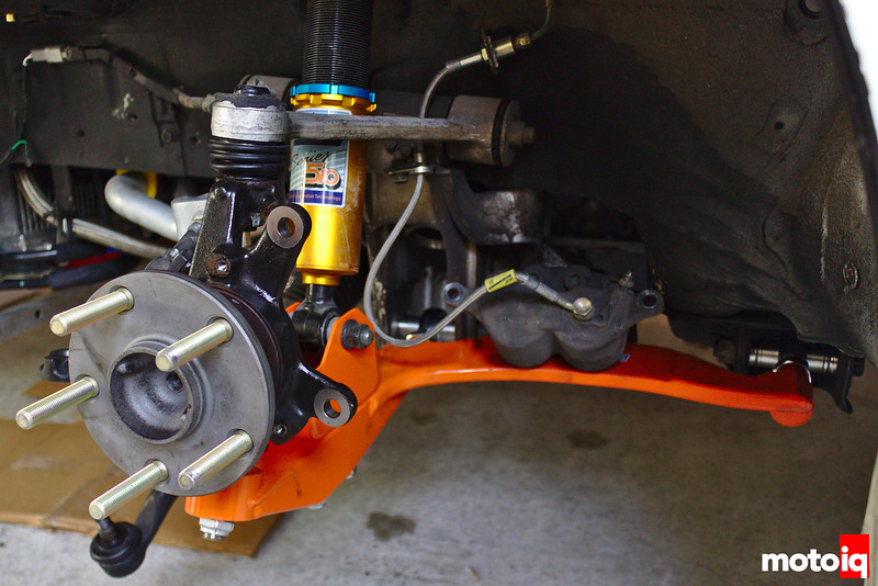 Knuckle/hub attached to control arms with brake caliper sitting on lower control arm in background