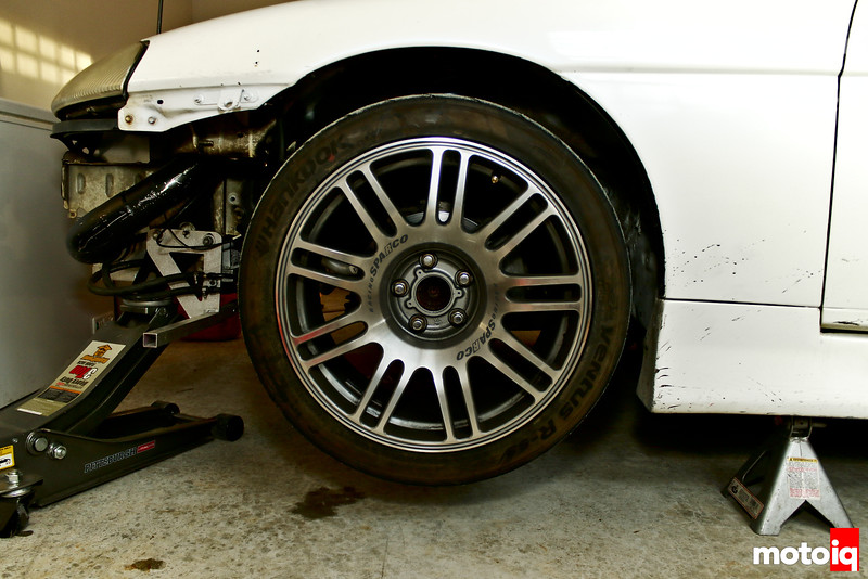 Left front wheel closeup with car on jack and on jackstand with wheel on