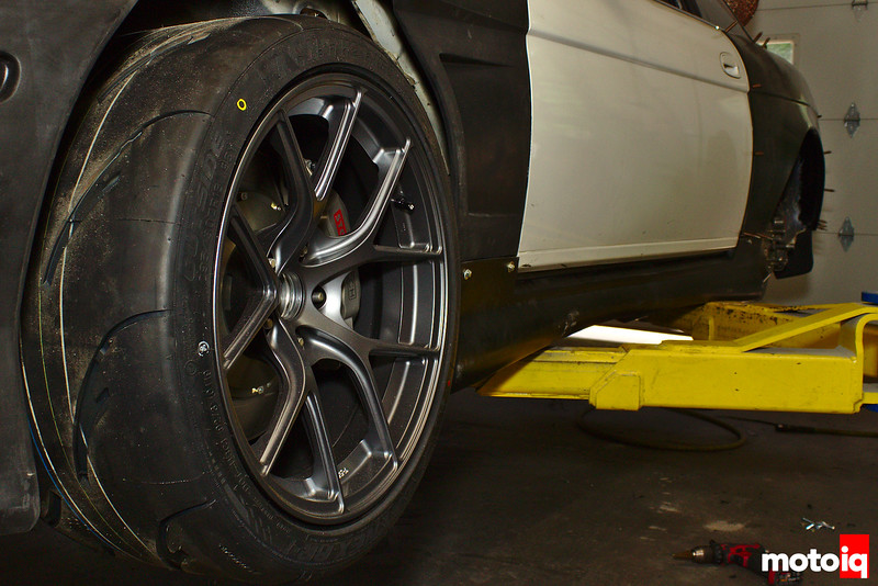 front driver's side wheel and side skirt visible with car on lift