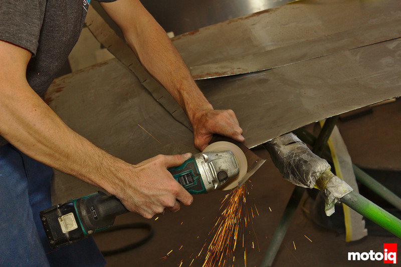 man using cut off wheel to notch metal strip