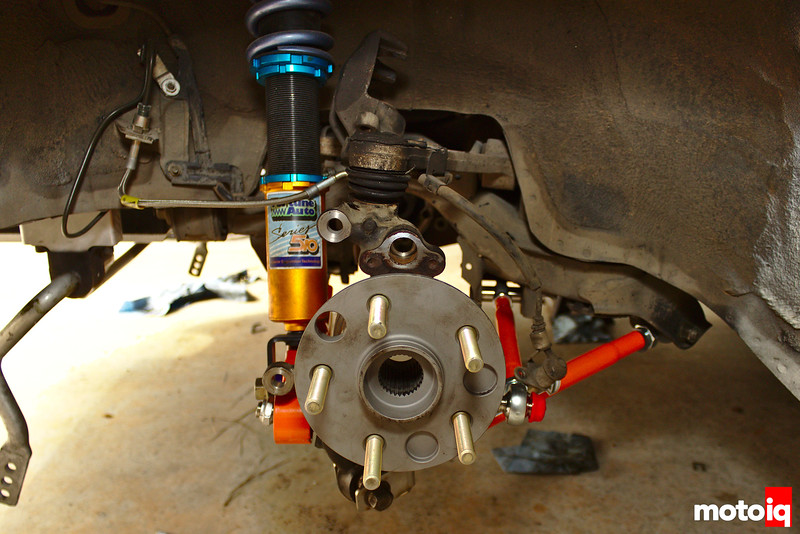 Rear knuckle attached to control arms with shiny gold shock body visible in background; swaybar dangling