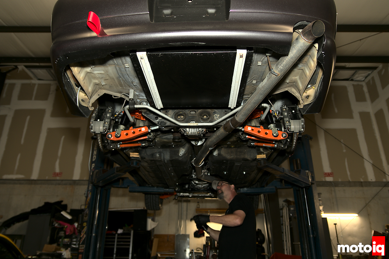 view of car on lift from underneath with guy in black t-shirt and black baseball hat holding a tool getting ready to work