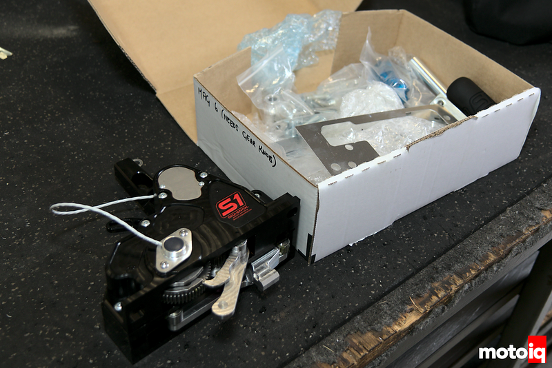 sequential shifter adapter assembly lying on black table next to cardboard box with installation parts in it