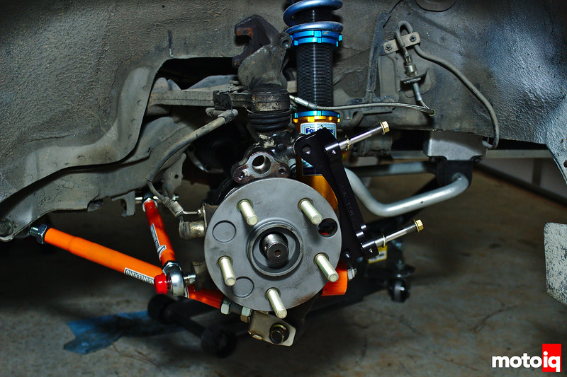 View of rear hub straight on with caliper bracket attached and bright orange control arms in background