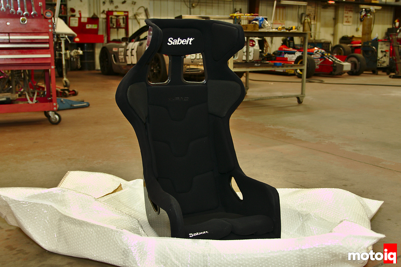 black Sabelt containment racing seat sitting on white bubble wrap bag on floor of shop