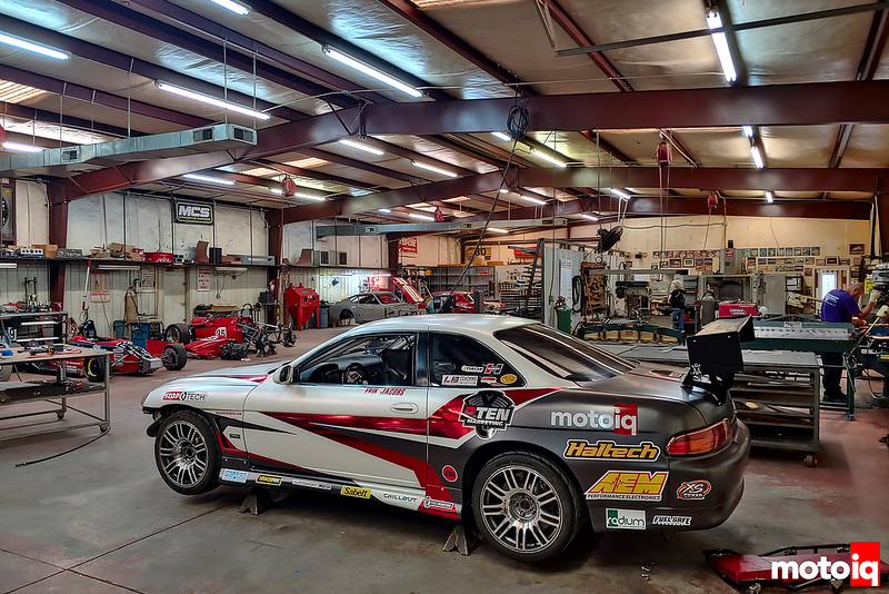 Lexus SC300 race car with gray and white and red chrome livery on jack stands in a large racing shop