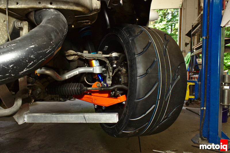 looking into front corner and seeing suspension with wheel turned to right and huge tire tread