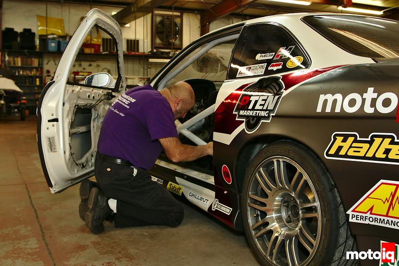 man wearing black jeans and purple shirt kneeling next to race car with door open