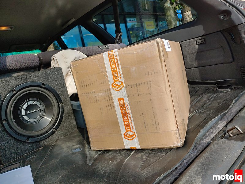 cardboard box in the trunk of a Subaru station wagon with a subwoofer visible in the background