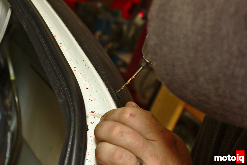 drilling a hole through the over fender into the car
