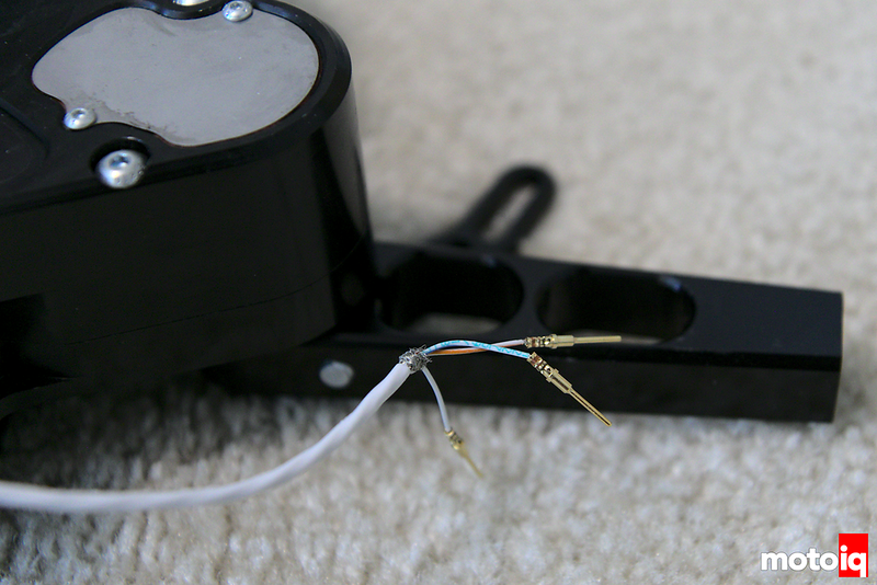 close up of 3 deutsch pins crimped onto a shielded cable with sequential shifter adapter in the background