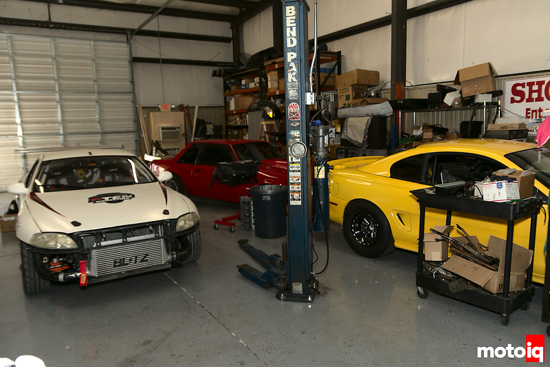 sc300 in a shop behind a lift with a red fox body mustang and a yellow sn95 mustang to the side