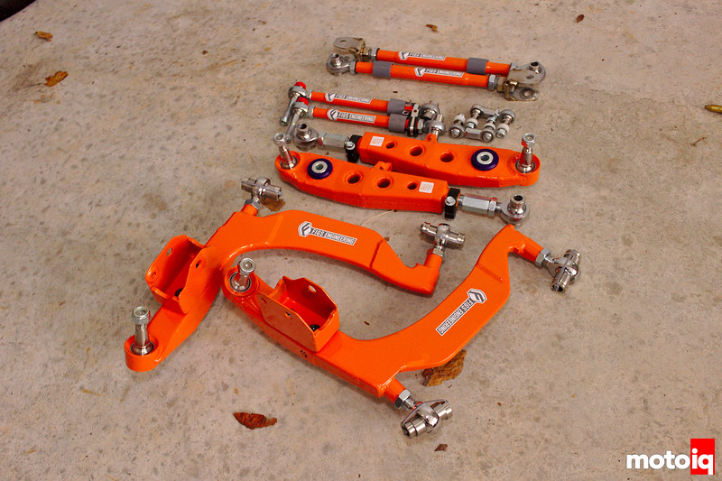 Full set of Figs lower control arms in signature orange color laying on garage floor