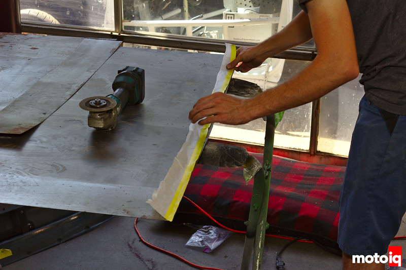 man applying stencil made of masking paper to a sheet of metal
