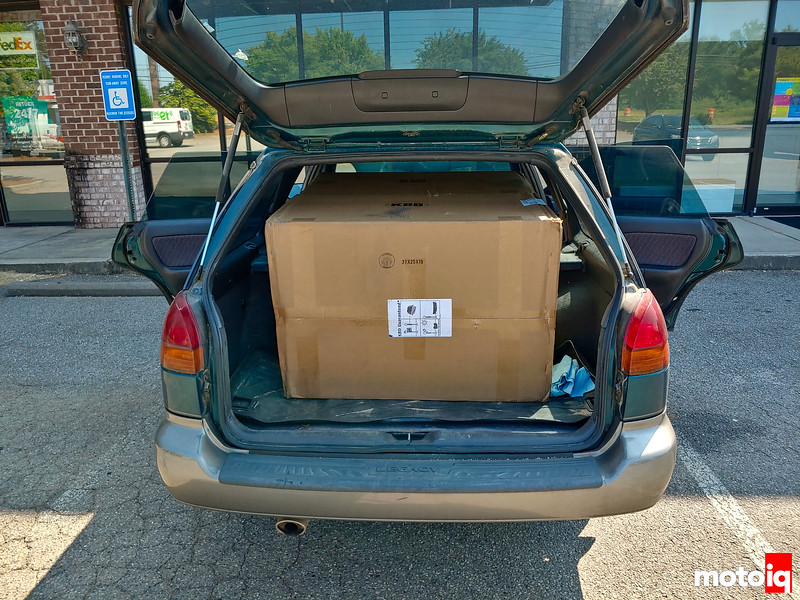 Subaru wagon trunk open and doors open with 2 large boxes inside