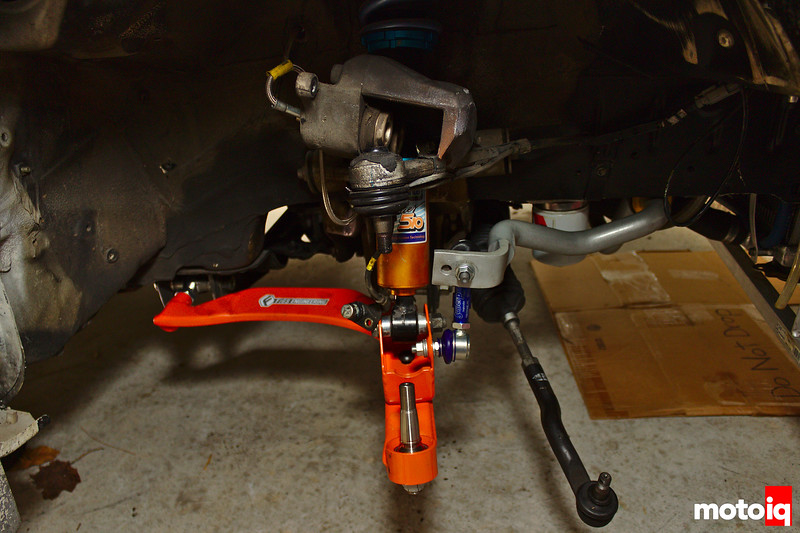 Lower control arm with shock and swaybar attached, tie rod and upper control arm dangling