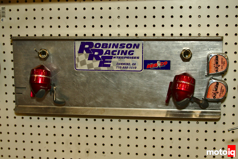 alignment plates hanging on pegboard wall with fishing reels and two tape measures