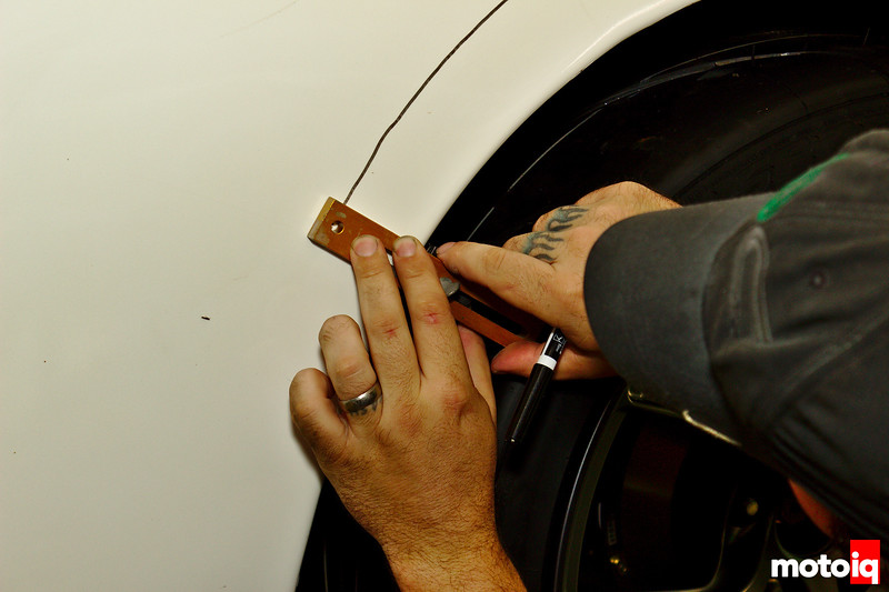 Using a tool to draw a sharpie line on the quarter panel