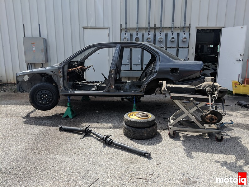 gutted shell on jackstands with driveshaft laying on ground and rear subframe on a cart