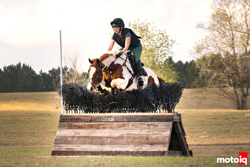 girl on paint horse jumping over a wooden triangle-shaped jump that is topped with brush