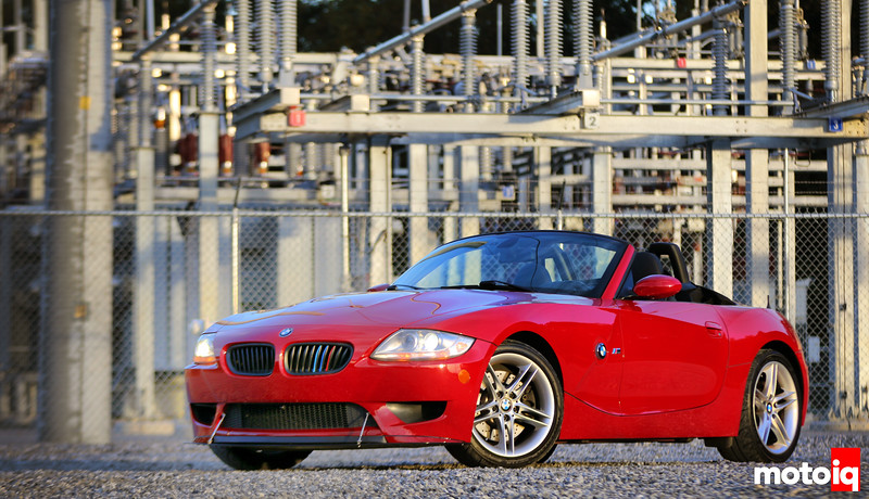 imola red BMW z4 M convertible parked on gravel with a power station in the background
