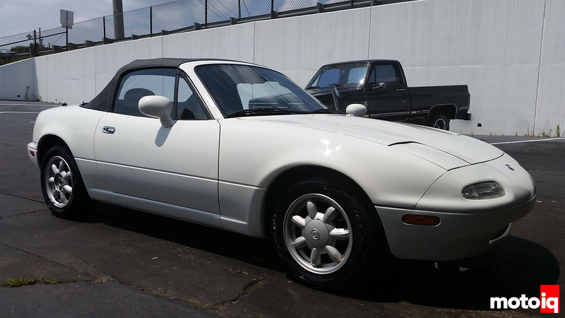 white first generation miata with a black top sitting freshly washed and looking very stock