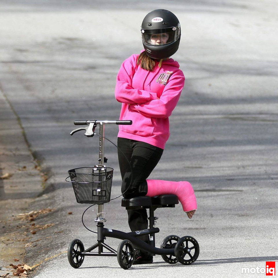girl in pink sweatshirt and black pants with pink cast on lower leg resting on a kneeling scooter with arms crossed and wearing a black racing helmet