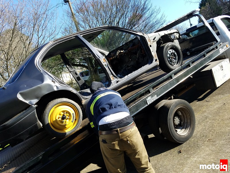 gutted nissan shell being tied down on a flatbed tow truck
