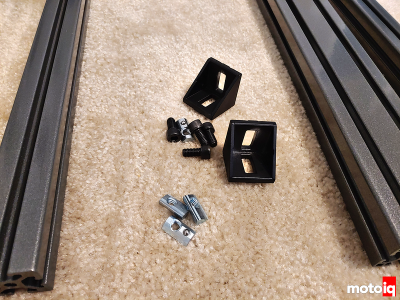 two 80-20 brackets, some socket cap screws, some t-slot retainers on the carpet between two sparkle gray t-slot pieces