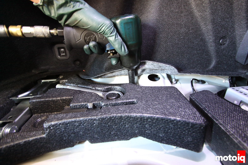"""Next we loosen the 14mm nuts above in the trunk. They're easily accessable even with the trunk lining still inside but for photographic purposes this gave us a better view. Again if you don't have a gun a 3/8"""" ratchet will suffice for you backyard mechanics."""