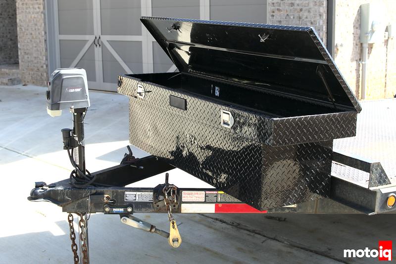 black toolbox on black a-frame tongue of black car trailer
