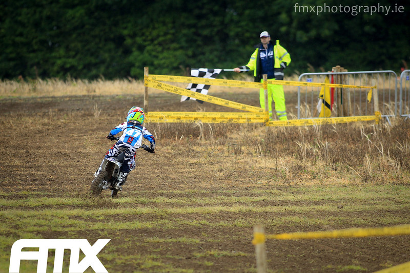 The back end kicks out on Jake Farrelly's 65cc machine before taking the chequered flag.
