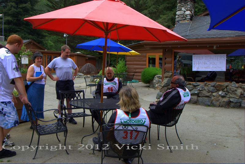 "Waystop in Big Sur, that's Chris Bushell, leader of the ""British Group"" on the Italian event and his girlfriend Elizabeth.  They checked out the MGA on the way to a vacation in Mexico.  The sign on the wall is thanking the firefighters, this was the first day the roads were open after the big fire"