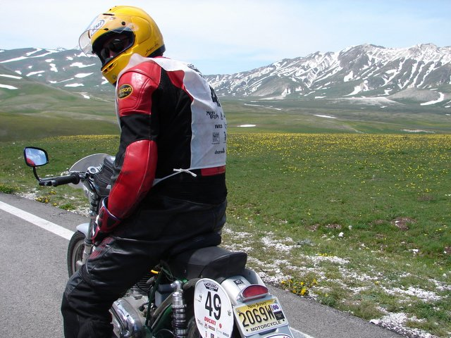 Racing among the snowcaps, this valley is famous for it's wildflowers, lush green fields, incredible views well above the treeline and curving roads billard table smooth.  That's Chris Jensen on his Ducati stopping to admire the view.