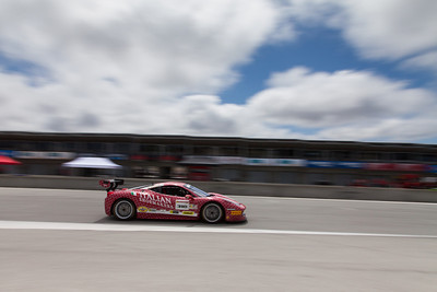 Gregory Romanelli races past the pit garages in the #318 Ferrari 458 EVO. © 2014 Victor Varela