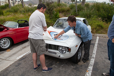 Event organizer, Gareth Ashworth, places the rally decal on the 1965 Alfa Romeo GTA