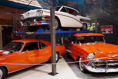 Cars on display at the Branson Auto Museum. On the left, a 1970 Plymouth Barracuda Coupe, on the right a 1957 Chevy Bel Air Hardtop, and on top a Buick.